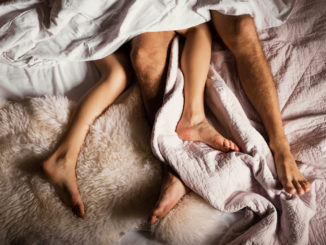 Legs of a couple in bed, couple lying in bed