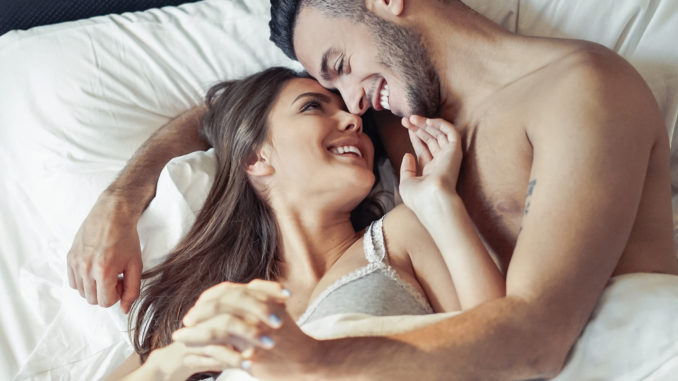 Happy romantic couple embracing in the bed