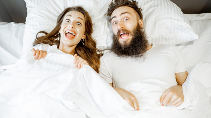 Portrait of a young couple feeling surprised and shocked lying together on the bed under the white sheets