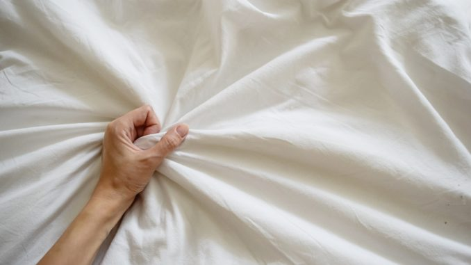 Close up woman hand pulling and squeezing white sheets in ecstasy in bed.