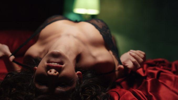 female person biting lip in bedroom.
