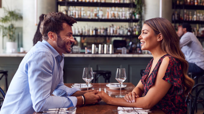 Couple On Valentines Day First Date Sitting At Table In Restaurant