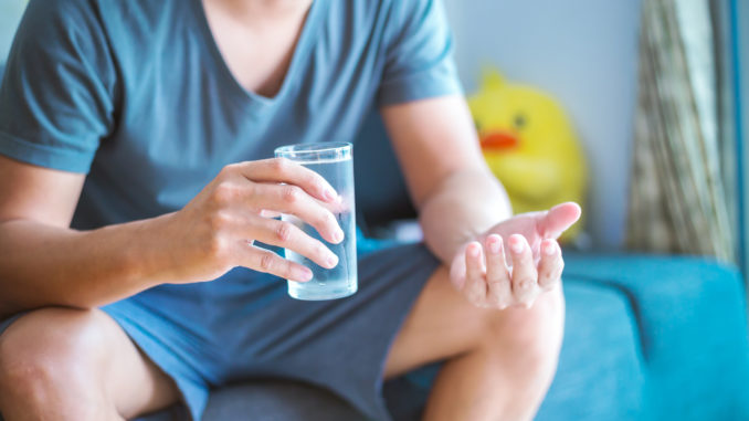 Man sitting and hold glass of water.