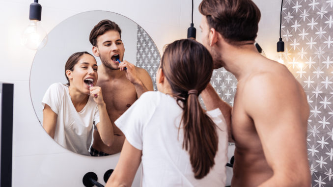 Man hugging. Man with no shirt on his body hugging his lovely wife while brushing teeth together
