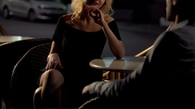 Attractive blond female seducing man on restaurant terrace, escort service