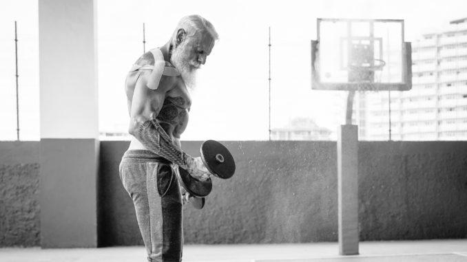 Senior fitness man doing biceps curl exercises inside old gym