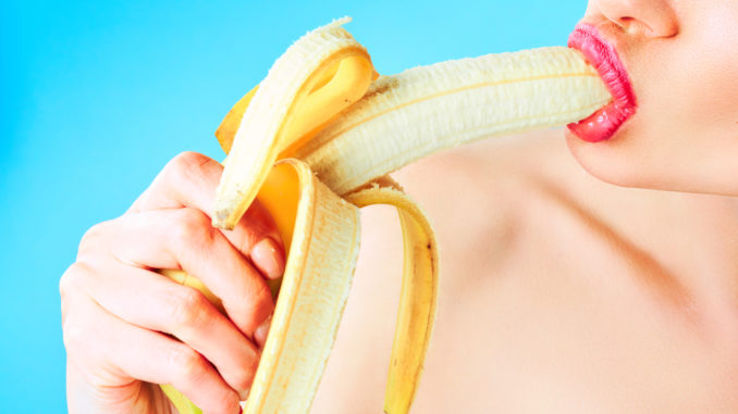 Close-up of woman eating banana isolated on blue.