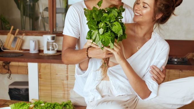Couple At Kitchen. Romantic Man Giving Bundle Of Herbs