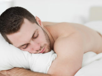 Man lying on his belly while sleeping in his bedroom