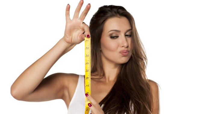 Young woman is thrilled by the length of the measuring tape