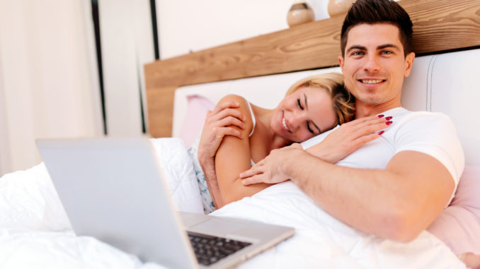 Happy couple in bed using laptop