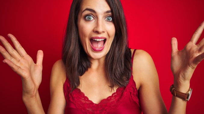 Young beautiful woman wearing lingerie over red isolated background celebrating crazy and amazed for success with arms raised and open eyes screaming excited.