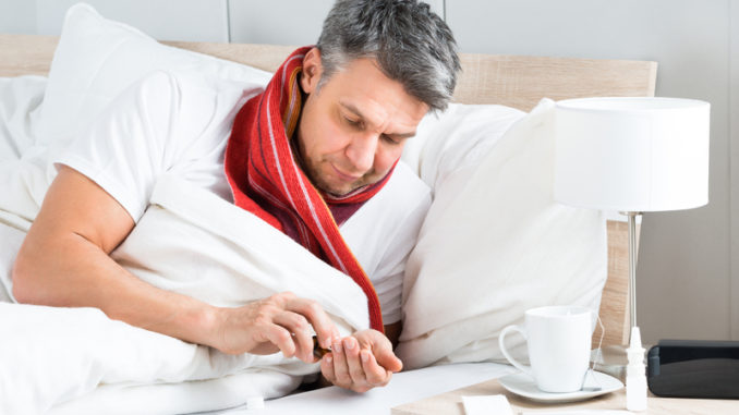 Mature Sick Man Lying On Bed Having Medicine