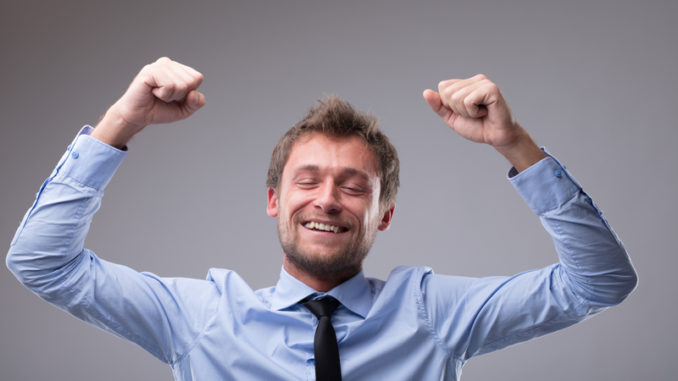 Jubilant happy man cheering and punching the air with his fists as he celebrates a victory or success