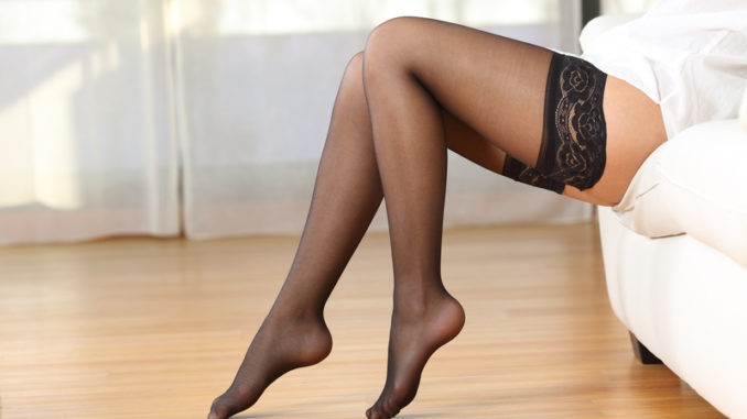 Side view of beautiful woman legs with nylons posing sitting on a couch at home