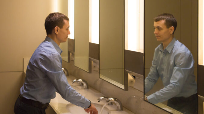 A 35-40 year old man is washing himself in the toilet looking at himself in the mirror