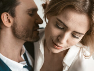 Man going to kiss female neck