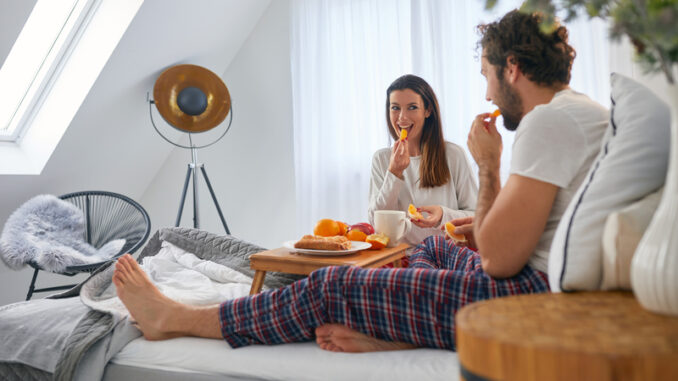 A young couple enjoying eating oranges during a breakfast in the bed at their bedroom.