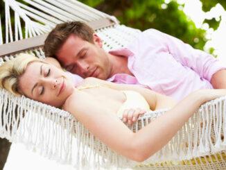 Couple Sleeping In Beach Hammock Together