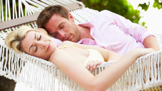Couple Sleeping In Beach Hammock Together