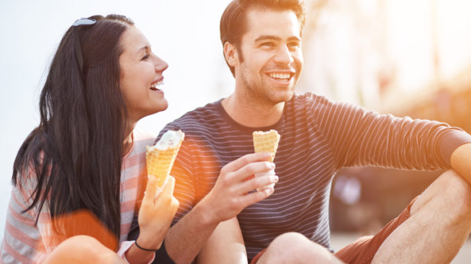 Photo of a romantic couple eating ice cream at park at sunset