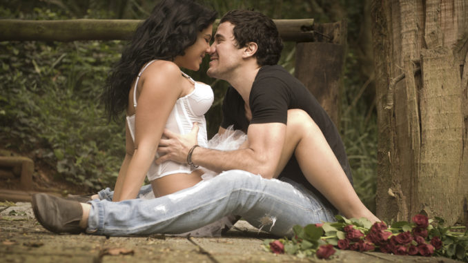 Young attractive couple flirting on wooden deck in forest with red roses