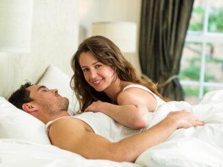 Romantic couple cuddling on bed in bedroom