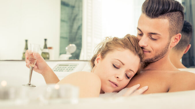 Young happy successful couple enjoying an hot bath in the jacuzzi
