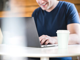 Happy man using laptop with take away coffee cup on table.