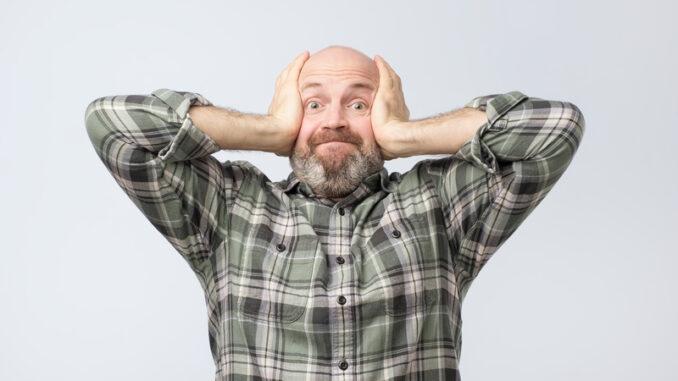Tensed mature european man covering ears
