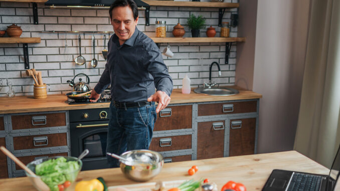 Cheerful man stand at stove and cook food in kitchen.