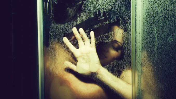 Young couple of naked women and men taking shower with water drops embracing in passion with wet bodies with hand on glass