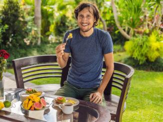 A man is having breakfast on the terrace.