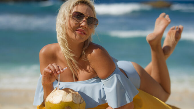 Young attractive and relaxed blond woman in bikini lying on beanbag hammock at tropical paradise beach drinking coconut water enjoying exotic Summer holidays destination on turquoise blue sea