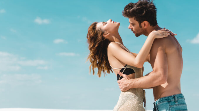 Side view of passionate young couple embracing on beach