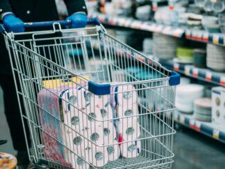 Man in protective gloves buying toilet paper in shop. Panic at coronavirus epidemic.