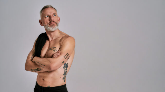 Middle aged muscular man took off black t shirt