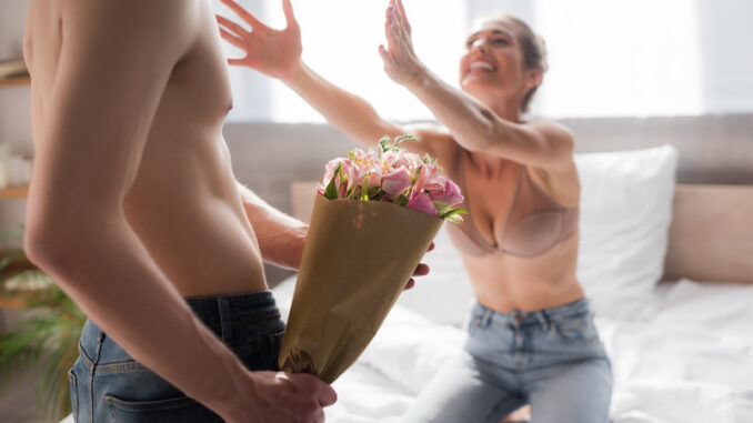Shirtless men holding flowers near excited women with outstretched hands on blurred background