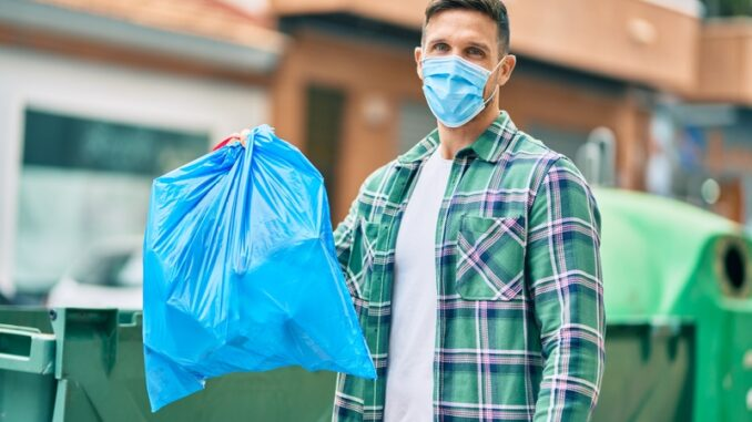 Young caucasian man wearing medical mask throwing waste bag to the container at the city