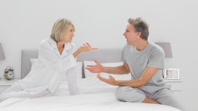 Couple arguing in bedroom sitting on bed