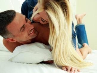 Young love couple in bed, romantic scene in bedroom