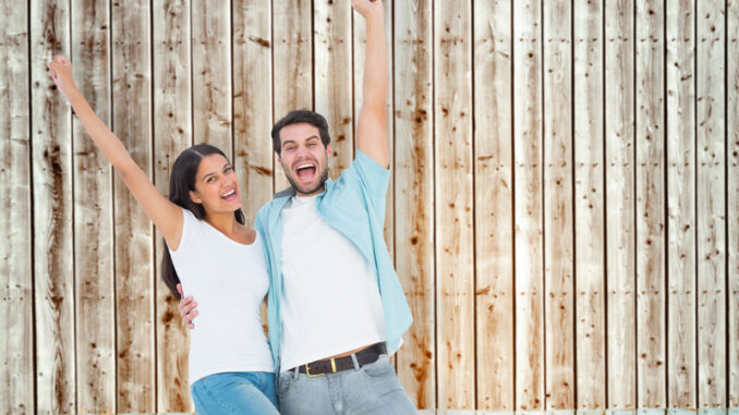 Happy casual couple cheering together against faded pine wooden planks