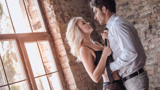 Handsome young businessman in suit and young women in black lingerie are going to have a sex