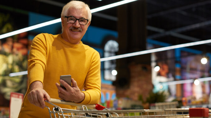 Portrait of modern senior man grocery shopping in supermarket pulling shopping cart and smiling