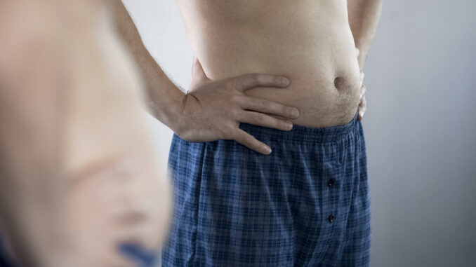 Aged man looking at his belly and remembering his pumped up figure and press