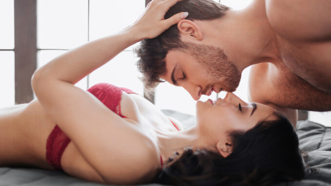 Romantic passionate kiss of couple in room.