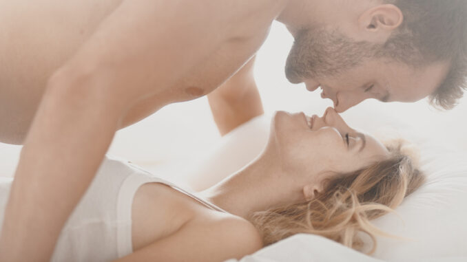 Romantic photo of pair kissing and caressing in bed