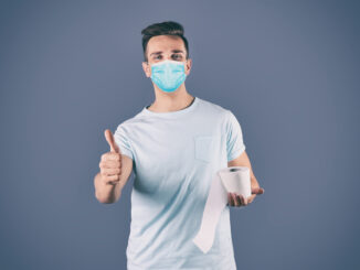 Man in medical mask holding toilet paper roll