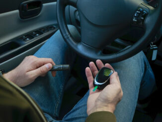 Diabetes concept. Diabetic man checking blood sugar level at car.
