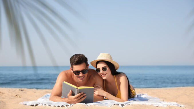 Happy couple reading book together on sunny beach
